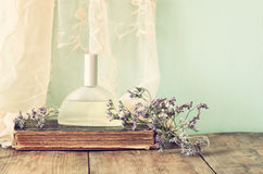 Fresh vintage perfume bottle next to aromatic flowers on wooden table. retro filtered image Royalty Free Stock Photography