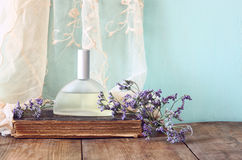 Fresh vintage perfume bottle next to aromatic flowers on wooden table. retro filtered image Stock Photography
