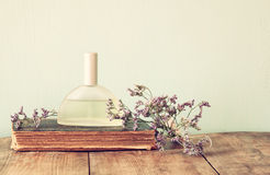 Fresh vintage perfume bottle next to aromatic flowers on wooden table. retro filtered image Stock Photo