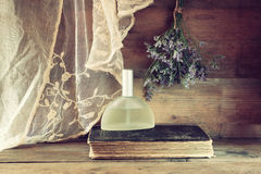 Fresh vintage perfume bottle next to aromatic flowers on wooden table. retro filtered image Royalty Free Stock Image