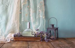 Fresh vintage perfume bottle next to aromatic flowers on wooden table. retro filtered image Stock Photos