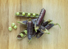 Fresh violet peas  on a wooden background Royalty Free Stock Image