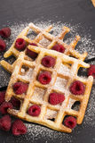 Fresh waffles garnished with powdered sugar and raspberries Royalty Free Stock Photography