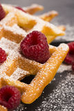 Fresh waffles garnished with powdered sugar and raspberries Stock Photography