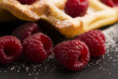 Fresh waffles garnished with powdered sugar and raspberries Stock Image