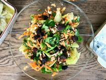 Fresh Walnut Salad with Grated Carrot Slices in Glass Bowl at Dinner Table royalty free stock photos
