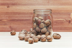 Fresh walnuts on wood table background. Fresh walnuts in shells falling out of glass jar on wood table background stock image