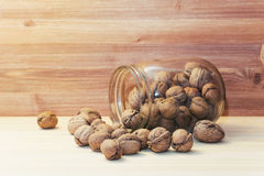 Fresh walnuts on wood table background. Fresh walnuts in shells falling out of glass jar on wood table background stock photography
