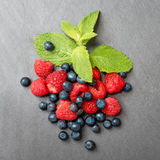 Fresh washed raspberries, blueberries and mint leaves. Organic berries on grey slate stone board. Top view. Fresh washed raspberries, blueberries and mint Royalty Free Stock Photos