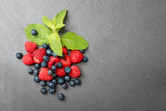 Fresh washed raspberries, blueberries and mint leaves. Organic berries on grey slate stone board. Top view, space for. Text Royalty Free Stock Image