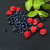 Fresh washed raspberries, blueberries, mint leaves with waterdrops. Organic berries on grey slate stone board. Fresh washed raspberries, blueberries, mint Royalty Free Stock Photography