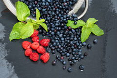 Fresh washed raspberries, blueberries, mint leaves with waterdrops. Organic berries on grey slate stone board. Fresh washed raspberries, blueberries, mint Royalty Free Stock Photos