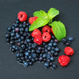 Fresh washed raspberries, blueberries, mint leaves with waterdrops. Organic berries on grey slate stone board. Fresh washed raspberries, blueberries, mint Stock Photo