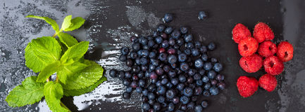 Fresh washed raspberries, blueberries, mint leaves with waterdrops. Organic berries on grey slate stone board. Smoothie. Ingredients. Banner for website Royalty Free Stock Image