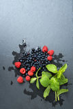 Fresh washed raspberries, blueberries, mint leaves with waterdrops. Organic berries on grey slate stone board, space for. Text Stock Photography
