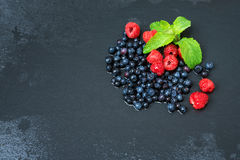 Fresh washed raspberries, blueberries, mint leaves with waterdrops. Organic berries on grey slate stone board, space for. Text Stock Image