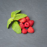 Fresh washed raspberries and mint leaves. Organic berries on grey slate stone board. Top view. Fresh washed raspberries and mint leaves. Organic berries on grey Royalty Free Stock Image