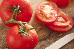 Fresh washed tomatoes on the vine and sliced Royalty Free Stock Image