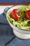 Fresh washed tomatos and greens in a colander. Fresh washed vegetables; two washed tomatos and greens in a colander; vertical; selective focus Stock Photos