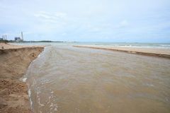 Fresh water canal running to sea coast Stock Images