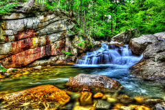 Fresh water cascading over large rocks in a small stream HDR. Stock Photography
