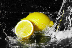 Fresh water drops on lemon on black Royalty Free Stock Image