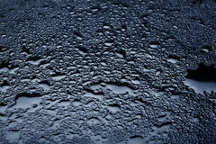 Fresh water drops sprayed. On a black stone surface Royalty Free Stock Photo