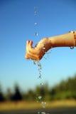 Fresh water falling on children hands
