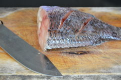 Fresh water fish and knife prepare for cook on wooden chop block Stock Photo