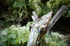 Fresh water flowing in wooden groove above mountain stream. Fresh water flowing in wooden groove above mountain stream, creating small waterfall at the end of royalty free stock image