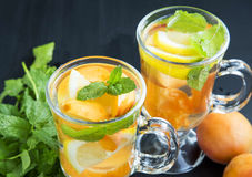 Fresh water with fruits and mint leaves. Fresh water with fruits and mint herb, cold summer drink with lemon, apricots and mint leaves Stock Images