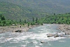 Fresh water green  river beas through  himalayan forest in Kullu. Lush green  himalayan forest  and  picturesque, wild winding river beas India Royalty Free Stock Photos
