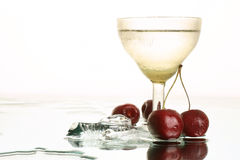 Fresh water ice drink. Fresh cold water with an ice and cherry. Still-life with refreshment beverage in the wineglass on white background Stock Image
