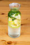 Fresh water with lemon, apple and mint. On a wooden table Royalty Free Stock Photos