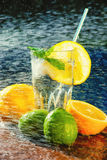 Fresh water with lemon, lime, mint and water splashes Stock Photos