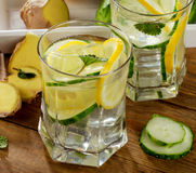 Fresh water with lemon, mint  and cucumber  on a wooden backgrou Royalty Free Stock Photos
