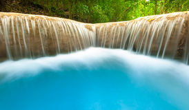 Fresh water river flows and falls from smooth waterfall cascade Stock Photos