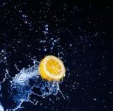 Fresh water splash on lemon sweet. Over black stock photos