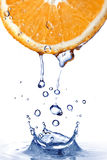 Fresh water splash on orange isolated on white Stock Photos