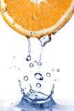 Fresh water splash on orange isolated on white Stock Photos