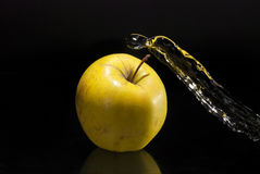 Fresh water splash on yellow apple Stock Images