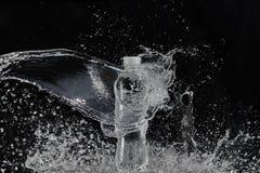 Fresh water splashing out of bottle. Black background royalty free stock image