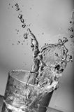 Fresh water splashing out of a glass with ice Royalty Free Stock Image