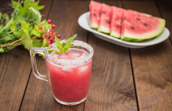 Fresh watermelon juice on a background of slices     wooden table. Close-up Stock Photos