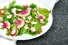 Fresh Watermelon Radish salad. Vegan, vegetarian, clean eating, dieting, food concept. Fresh Watermelon Radish salad with arugula feta, chia  on black background royalty free stock image