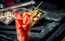Fresh watermelon slice in clear plastic glass container on black fiber floor. Of pickup truck Stock Photos