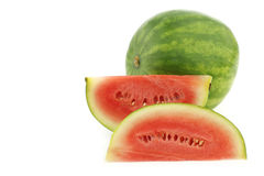Fresh watermelon and some cut pieces Stock Images