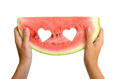 Fresh watermelon in womans hands. Fresh watermelon with hearts in womans hands  on white background Royalty Free Stock Photo