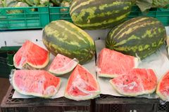 Fresh watermelons. With some vegetables in the back being sold at a market royalty free stock photo