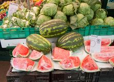 Fresh watermelons. With some vegetables in the back being sold at a market royalty free stock photos